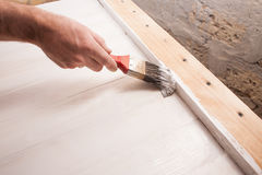 Man`s hand painting wooden table with brush Stock Photos