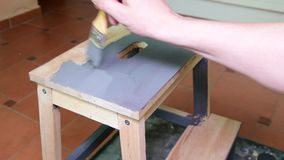 Man's hand paints the furniture step stool . Gray coating. Painting step stool with grey color. stock video footage