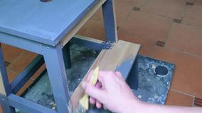 Man's hand paints the furniture step stool . Gray coating. Painting step stool with grey color. stock footage