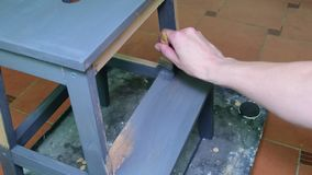 Man`s hand paints the furniture step stool . Gray coating. Painting step stool with grey color. stock video