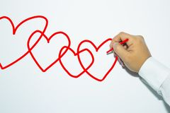 Man`s hand with pencil draws hearts on white background. Man`s hand with pencil draws hearts on white background Royalty Free Stock Photo