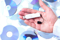 Man's hand with pendrive over CD's background. Royalty Free Stock Images