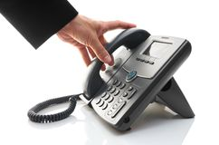 Man's hand is picking up the phone Stock Photo