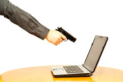 Man's hand with pistol aimed at laptop Stock Images