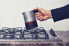 Man's hand placing espresso maker on stove Stock Photos