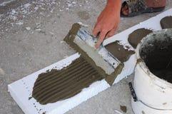 Man's Hand Plastering a Wall Styrofoam or Foam Board Insulation with Trowel. Styrofoam Insulation for Basement Walls. Stock Photos