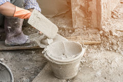 Man's hand plastering a wall with trowel. Stock Image