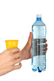 Man's hand with  plastic cup and bottle wate Stock Photo