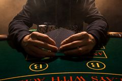 Man`s hand with playing cards close up. Casino card game chips. Put on the table playing cards. Poker chips on the table. A man in a hood with cards in his stock images