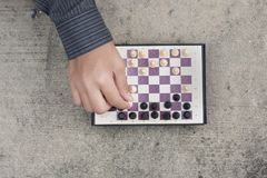 Man`s hand playing chess and check mate the opponent. Top view Royalty Free Stock Image