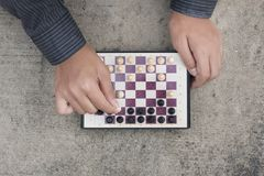 Man`s hand playing chess and check mate the opponent. Top view Stock Photos