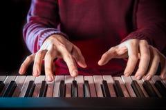 Man's hand playing piano. Close-up Stock Photos