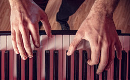 Man's hand playing piano. Close-up Stock Photography