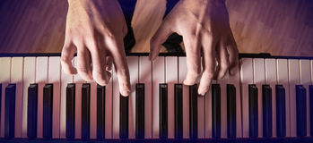 Man's hand playing piano. Close-up Royalty Free Stock Image