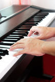 Man's hand playing piano. Stock Photos