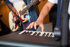 Man's Hand Playing Piano In Recording Studio. Closeup of man's hand playing piano in recording studio Stock Photo