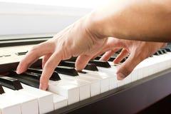 Man's hand playing piano. Stock Photos