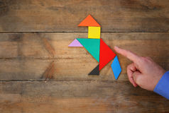 Man's hand pointing at horse made from tangram puzzle Royalty Free Stock Image