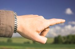 Man's hand pointing somewhere. On meadow royalty free stock photos