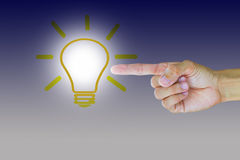 Man`s hand pointing to light bulb Royalty Free Stock Photos