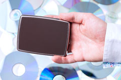 Man's hand with portable disk over CD's background. Royalty Free Stock Image