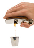 Man's hand pouring a brown liquid into metal cup. Man's hand pouring a brown liquid into small metal cup (isolated over white, clipping path royalty free stock photos