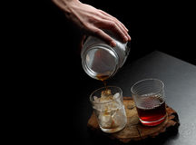 Man`s hand pouring hot and cold coffee into two glasses. Dark ba Royalty Free Stock Photos