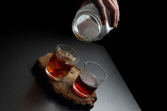 Man`s hand pouring hot and cold coffee into two glasses. Dark ba Stock Images
