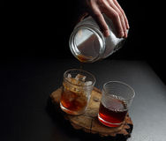 Man`s hand pouring hot and cold coffee into two glasses Royalty Free Stock Photo