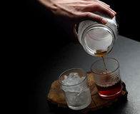 Man`s hand pouring hot and cold coffee into two glasses Royalty Free Stock Photos