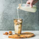 Man`s hand pouring milk to Iced latte summer coffee cocktail. Man`s hand pouring milk to Iced caramel latte coffee cocktail with frozen coffee ice cubes in glass Stock Photos