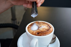 Man's hand pouring  sugar into white cup with cappuccino Stock Image