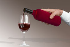 Man's hand pouring wine from a bottle into a glass Stock Image