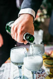 Man's hand pours champagne into glasses Stock Image