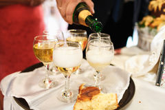 Man's hand pours a champagne into wineglasses on the tray Royalty Free Stock Image