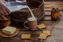 A man`s hand pours milk into a cup on the background of burlap and a wooden background. Around scattered crackers Royalty Free Stock Image