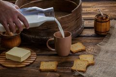 A man`s hand pours milk into a cup on the background of burlap and a wooden background. Around scattered crackers Royalty Free Stock Images