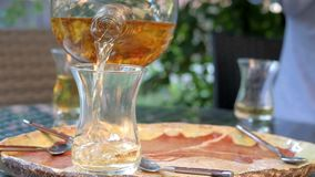 A man`s hand pours tea from a glass teapot into a glass cup. Sunny day stock video