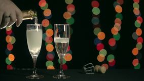 Man`s hand pours two glasses of champagne. Background lights bokeh. Closeup stock video footage