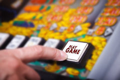 Man's hand pressing play button on a slot machine Royalty Free Stock Images
