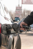 Man's hand pumping gas into car Stock Images
