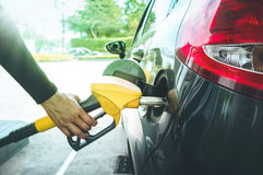 Man`s hand pumping gasoline fuel in car at gas station. Transportation and oil concept Royalty Free Stock Photo