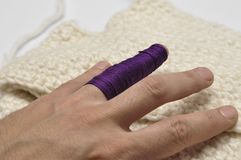 Man& x27;s hand and purple yarn isolated on a white background.Crochet.Copy space. Man& x27;s hand and  purple yarn isolated on a white background.Crochet hobby stock image