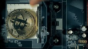 The man`s hand puts the bitcoins in a column. Hand counting bitcoins on the motherboard. Crypto currency Gold Bitcoin - stock footage