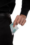 Man's hand puts money into the pocket of the ruble Royalty Free Stock Image