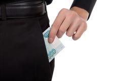 Man's hand puts money into the pocket  ruble. Man's hand puts money in your pocket Royalty Free Stock Photos