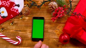 Man`s hand puts the phone on the table, toys lie on the table and garlands burn. Top view. Man`s hand puts the phone on the table and moves his finger across the stock video
