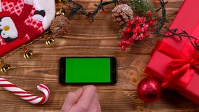 Man`s hand puts the phone on the table, toys lie on the table and garlands burn. Top view. Man`s hand puts the phone on the table and moves his finger across the stock video footage