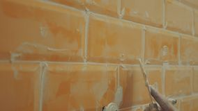 Man`s hand puttied seams of orange tiles on the wall stock video