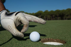 Man`s hand putting golf ball in hole Royalty Free Stock Photos